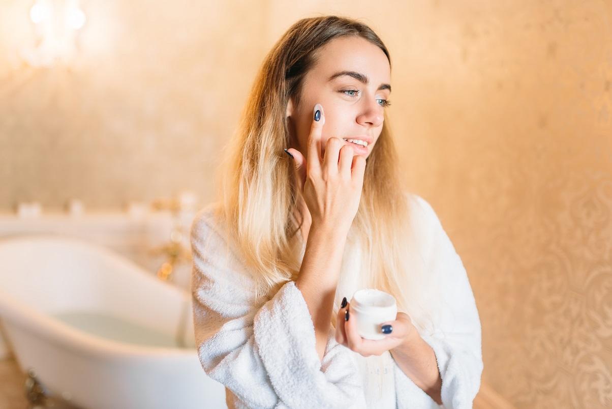 Kobieta nakładająca balsam na twarz